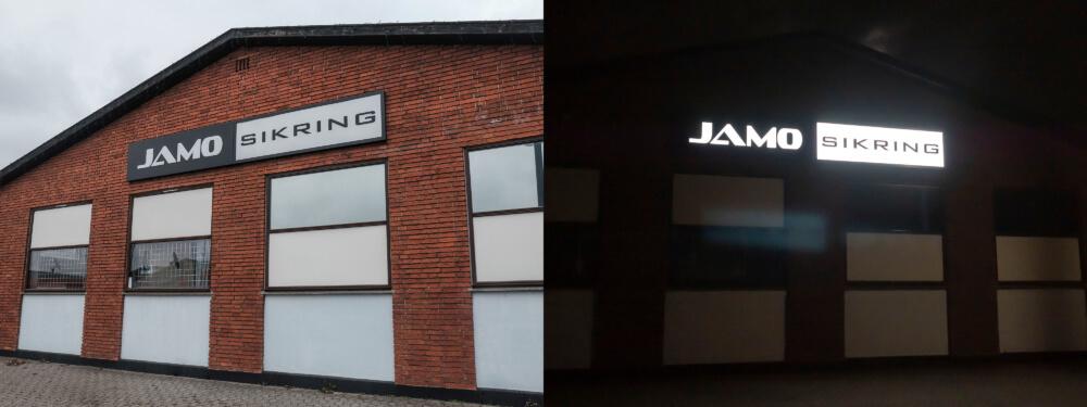 Jamo Sikring – lakeret alukassette med lys gennem udfræste akrylbogstaver i front.